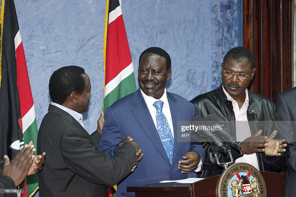 Outgoing Kenyan Prime Minister Raila Odinga (C) shakes hands with Kalonzo Musyoka (L), Kenya's outgoing vice president and Odinga's running mate, as he addresses the media at a press conference at his office in Nairobi on March 30, 2013. The Kenyan Supreme Court ruled on March 30 on a petition by outgoing Kenyan Prime Minister Raila Odinga challenging the election of contender Uhuru Kenyatta during the March 4 elections. The Supreme Court upheld the victory of Uhuru Kenyatta in the March 4 election, said Chief Justice Willy Mutunga. Odinga conceded defeat and wished Uhuru Kenyatta well in running the affairs of government. AFP PHOTO / Till Muellenmeister