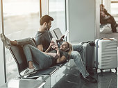 I like to spend time with you. Full length beaming woman looking at mobile while lying on male legs. He reading book. Satisfied couple locating in airport concept