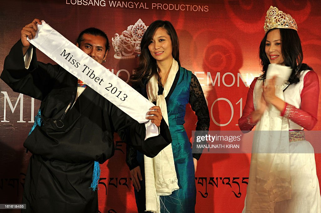 Outgoing Miss Tibet Tenzin Yangkyi (R) applauds as Lobsang Wangyal (L), director of the Miss Tibet Pageant, displays a sash before unanimously crowning Tenzing Lhamo (C) as this year's Miss Tibet during the coronation ceremony held in Bangalore on February 13, 2013. Lhamo was the lone contestant and was unanimously crowned with the Miss Tibet 2013 title. AFP PHOTO/Manjunath KIRAN