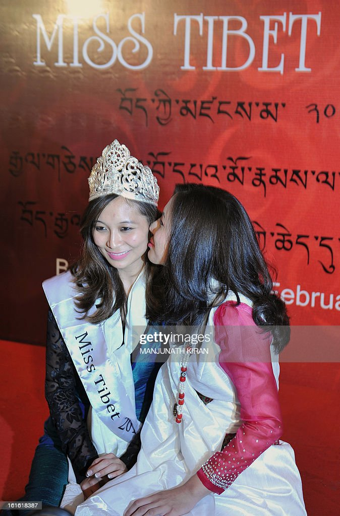 Outgoing Miss Tibet Tenzin Yangkyi (R) gives a peck on the cheek of the unanimously crowned Miss Tibet 2013 Tenzing Lhamo during the coronation ceremony held in Bangalore on February 13, 2013. Lhamo was the lone contestant and was unanimously crowned with the Miss Tibet 2013 title. AFP PHOTO/Manjunath KIRAN
