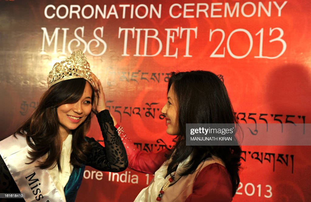 Outgoing Miss Tibet Tenzin Yangkyi (R) looks on as unanimously crowned Miss Tibet 2013 Tenzing Lhamo adjusts her tiara during the coronation ceremony held in Bangalore on February 13, 2013. Lhamo was the lone contestant and was unanimously crowned with the Miss Tibet 2013 title. AFP PHOTO/Manjunath KIRAN