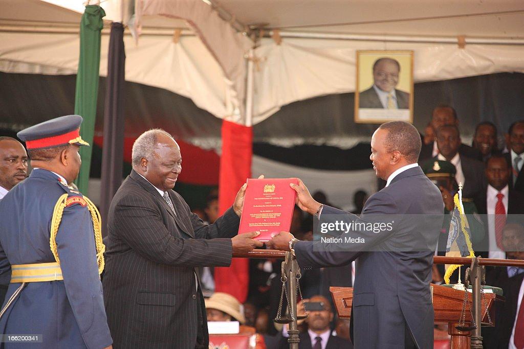 Outgoing President Kibaki hands over the Constitution of Kenya to President Uhuru Kenyatta after he was sworn in as Kenyan's 4th President on April 9, 2013 in Nairobi, Kenya. Kenyatta received masses of support from the citizens of Kenya despite being under investigation for crimes against humanity.
