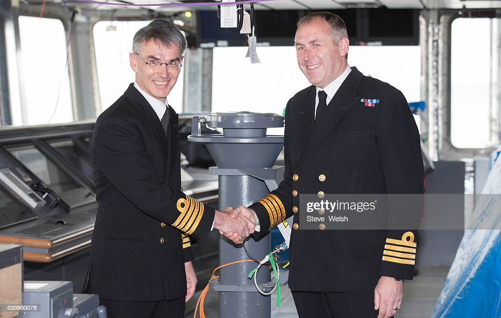 Outgoing Senior Naval Officer, Captain Simon Petitt (R) hands over HMS Prince of Wales to her new Senior Naval Officer, Captain Ian Groom on the Bridge of HMS Queen Elizabeth on May 24, 2016 in Rosyth, United Kingdom. HMS Queen Elizabeth and HMS Prince of Wales are currently being built in Rosyth for the Royal Navy.