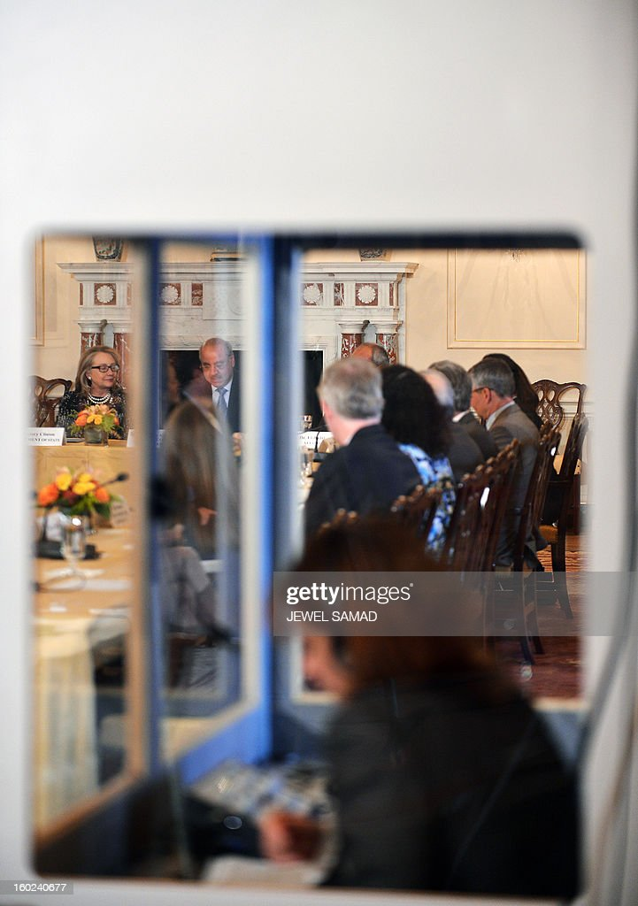 Outgoing US Secretary of State Hillary Clinton (L) is seen through a translation booth she hosts the announcement of the Open Book Project at the State Department in Washington, DC, on January 28, 2013. The Open Book Project is an initiative of the US Department of State, the Arab League Educational, Cultural and Scientific Organization and leading education innovators to expand access to free, high-quality open educational resources in Arabic, with a focus on science and technology and online learning. AFP PHOTO/Jewel Samad