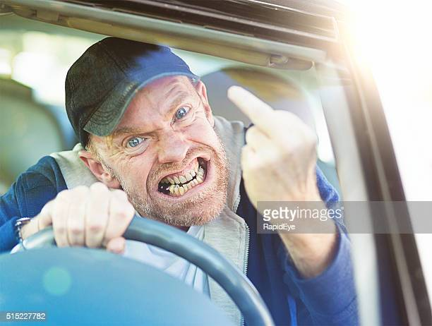 Out-of-control, grimacing male driver giving furious middle-finger gesture though windscreen