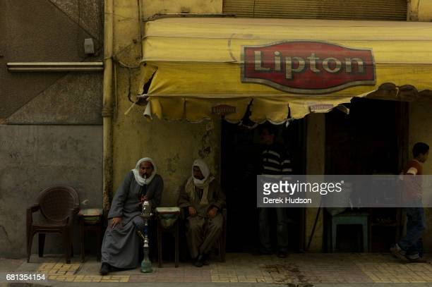 Outside a cafe a man smokes a water pipe as another sits beside him and watches Alexandria Egypt December 17 2009 The awning above them advertises...