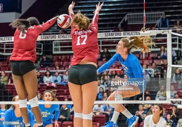 UCLA outside hitter Reily Buechler delivers a slam between Stanford middle blocker Tami Alade and Stanford opposite Merete Lutz during the regular...