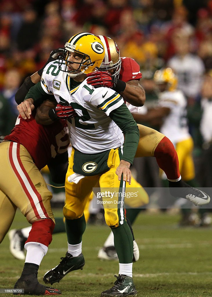 Outside linebacker Ahmad Brooks #55 of the San Francisco 49ers tackles quarterback Aaron Rodgers #12 of the Green Bay Packers after throwing the ball during the NFC Divisional Playoff Game at Candlestick Park on January 12, 2013 in San Francisco, California.