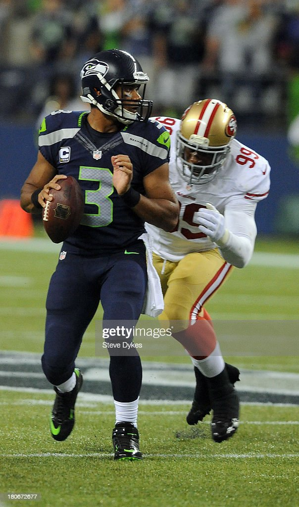 Outside linebacker Aldon Smith #99 of the San Francisco 49ers cloes in to sack quarterback Russell Wilson #3 of the Seattle Seahawks during the second quarter of the game at CenturyLink Field on September 15, 2013 in Seattle, Washington.