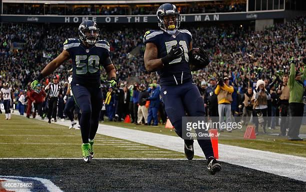 Outside linebacker Bruce Irvin of the Seattle Seahawks celebrates with outside linebacker KJ Wright of the Seattle Seahawks after running an...