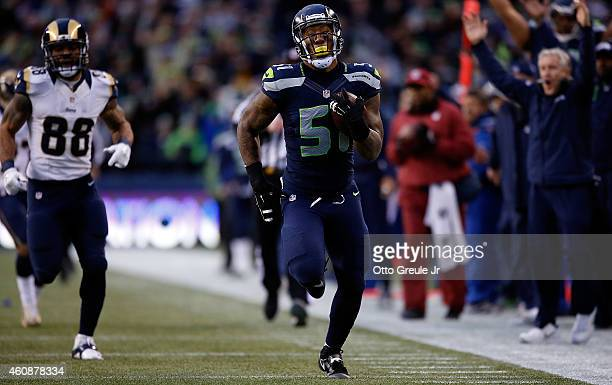 Outside linebacker Bruce Irvin of the Seattle Seahawks runs an interception back 49 yards for a touchdown as tight end Lance Kendricks of the St...