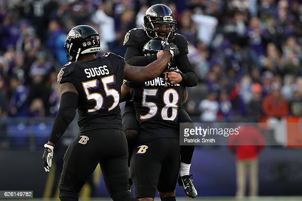 Outside linebacker Elvis Dumervil of the Baltimore Ravens reacts with teammates Strong safety Eric Weddle and outside linebacker Terrell Suggs after...