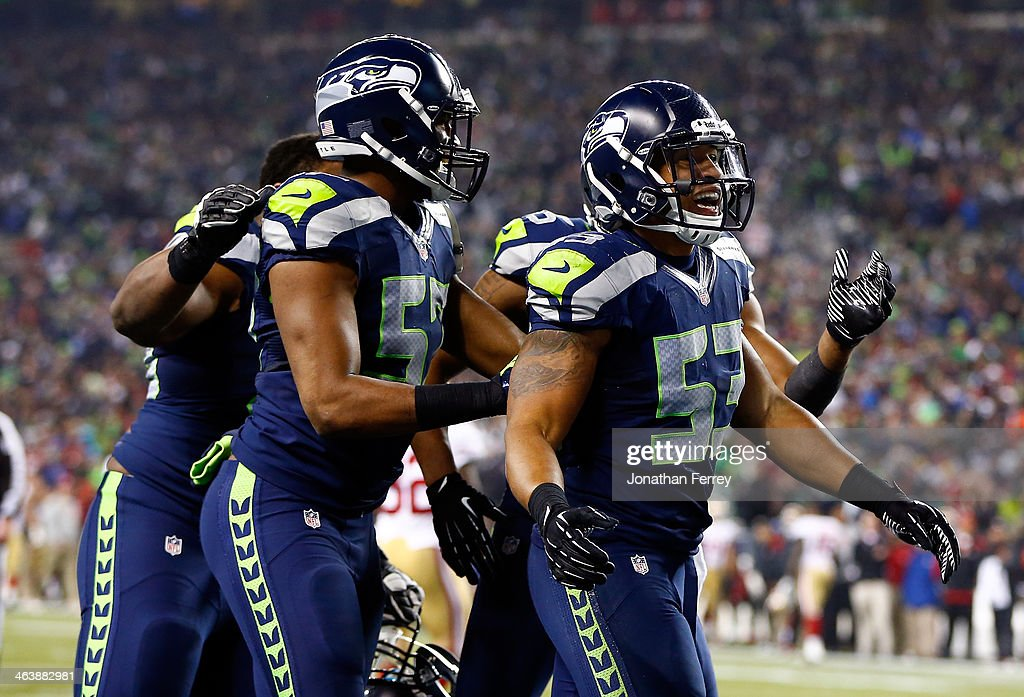 Outside linebacker Malcolm Smith and defensive back DeShawn Shead celebrate after Smith intercepts a pass in the endzone to win the game for the...