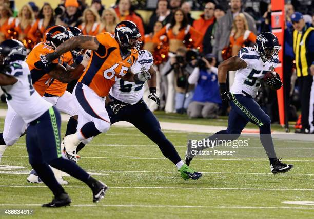 Outside linebacker Malcolm Smith of the Seattle Seahawks runs back an interception off quarterback Peyton Manning of the Denver Broncos during the...