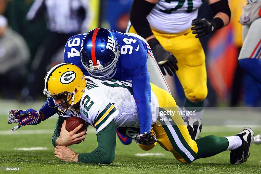 Outside linebacker Mathias Kiwanuka #94 of the New York Giants sacks quarterback Aaron Rodgers #12 of the Green Bay Packers in the third quarter at MetLife Stadium on November 25, 2012 in East Rutherford, New Jersey.