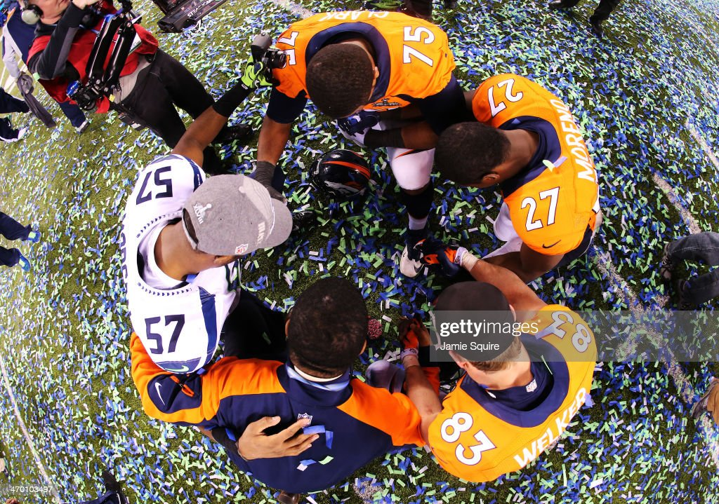 Outside linebacker Mike Morgan #57 of the Seattle Seahawks gathers with Broncos players after Super Bowl XLVIII at MetLife Stadium on February 2, 2014 in East Rutherford, New Jersey. The Seahawks beat the Broncos 43-8.