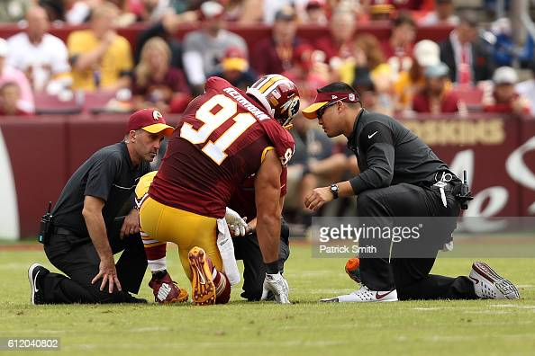 Outside linebacker Ryan Kerrigan of the Washington Redskins is attended to by staff while injured during a game against the Cleveland Browns in the...