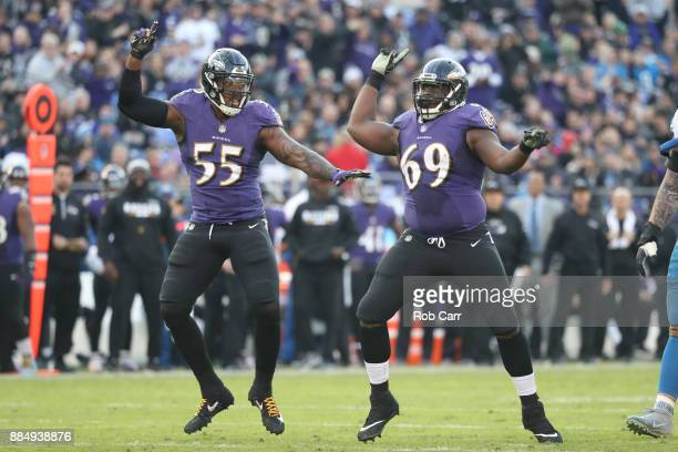 Outside Linebacker Terrell Suggs and defensive tackle Willie Henry of the Baltimore Ravens celebrate after a sack in the fourth quarter against the...