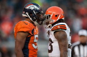 Outside linebacker Wesley Woodyard of the Denver Broncos and running back Trent Richardson of the Cleveland Browns exchange words after a play during...