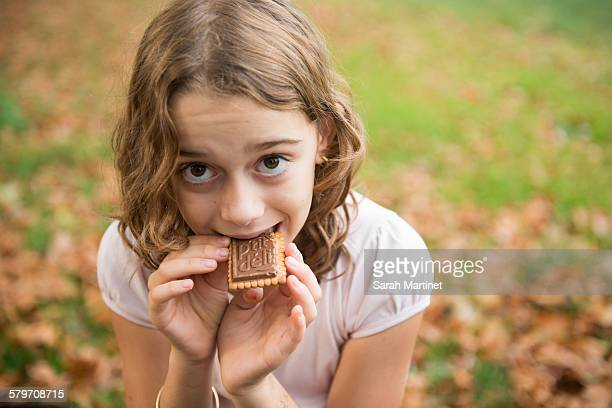 Outside portrait of a girl eating a biscuit