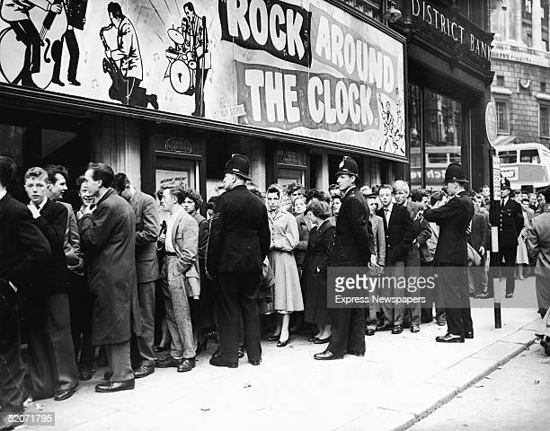 Outside the Gaiety Cinema police officers keep an eye on the crowd gathered to see the film 'Rock Around the Clock' starring American rock and roll...