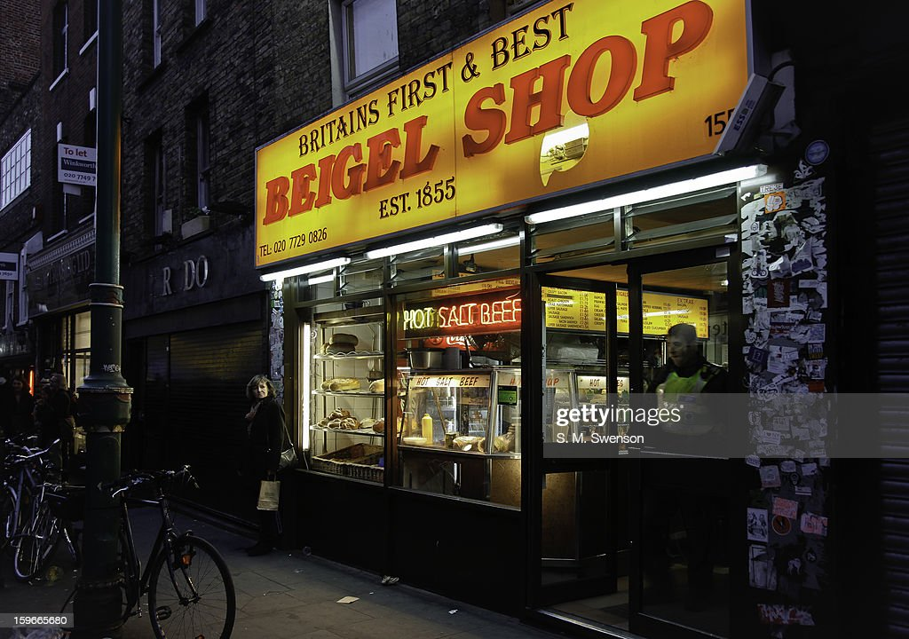 CONTENT] Outside the original bagel or 'beigel' shop (1855) in Brick Lane, East London. It is early evening and a policeman is coming out the door. A lady is waiting outside. There is a neon sign offering 'Hot Salt Beef'. These bagel shops date back to when there was a bustling Jewish immigrant community in the area. Taken on November 27, 2011.