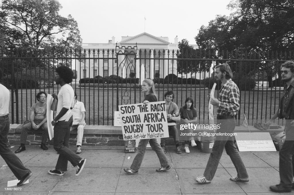 Outside the White House an antiapartheid demonstrator carries a placard protesting against the US tour by South African rugby team the Springboks...