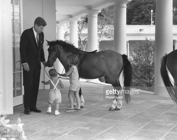 Outside the White House's Oval Office American President John F Kennedy and his children John and Caroline play with pony Macaroni Washington DC June...