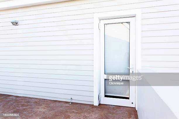 Outside wall and glass door of white painted clapboard house