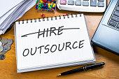 Outsource memo in notebook with part of laptop, receipts and calculator