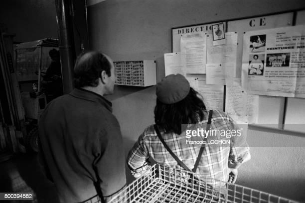 Ouvriers prenant connaissance du tableau d'affichage de la direction et du comité d'entreprise dans une usine de pompes en octobre 1976 à Châteauroux...