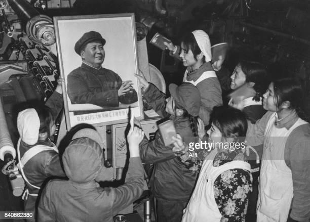 Ouvrières d'une usine de Pékin admirent le portrait de Mao en brandissant le Petit Livre rouge le 27 décembre 1967 Chine