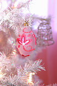 Oval bauble decorated with glittery pink leaf shapes and swirls, suspended from silver branch of Christmas tree