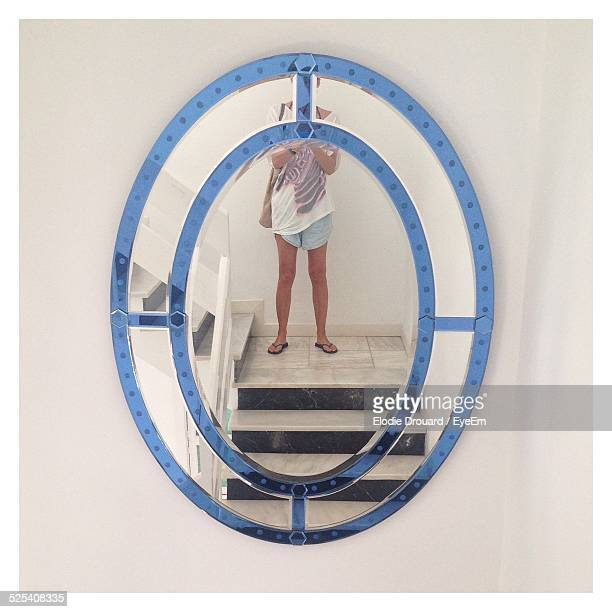 Oval Mirror With Cropped Reflection Of Woman Standing On Stairway