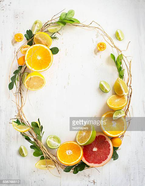 Oval shape citrus fruits ornament frame on white wooden background.