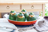 Stuffed oven baked round zucchini on an oven dish.