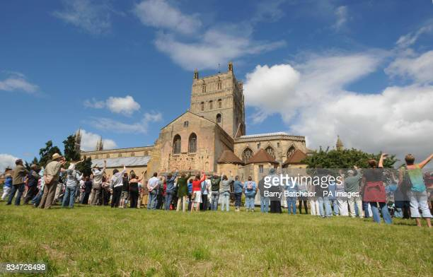 Over 500 people join hands outside Tewkewsbury Abbey in a 'chain of hope' marking the town's rebirth one year after last summer's devastating floods