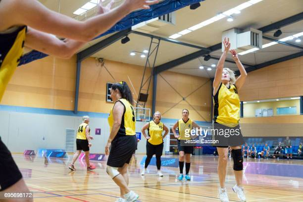 Over 60's female basketball players on indoor court in action