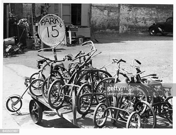 Over a dozen tricycles sit on a wagon in a parking lot on Arch Street in Philadelphia A nearby sign advertises that one can park there for fifteen...
