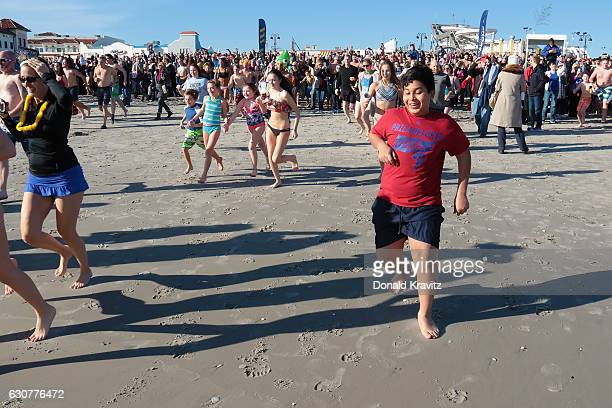 Over a thousand spectators watched more than 500 brave participants as they run into the Atlantic Ocean during First Day At The Beach on January 1...