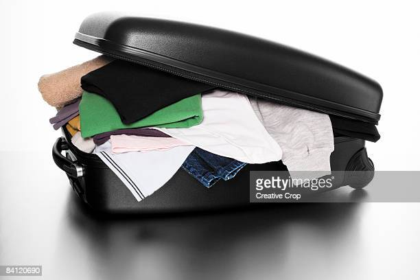 Over filled suitcase with clothes over flowing