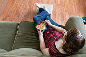 horizontal over head  image of a caucasian woman sitting on a sofa eating cereal cheerios in a red heart shaped bowl.