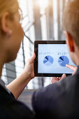 Over shoulder view of businesswoman and man using touchscreen on digital tablet in office