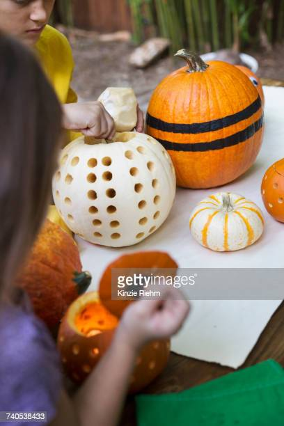 Over shoulder view of girl and brother preparing pumpkins on garden table