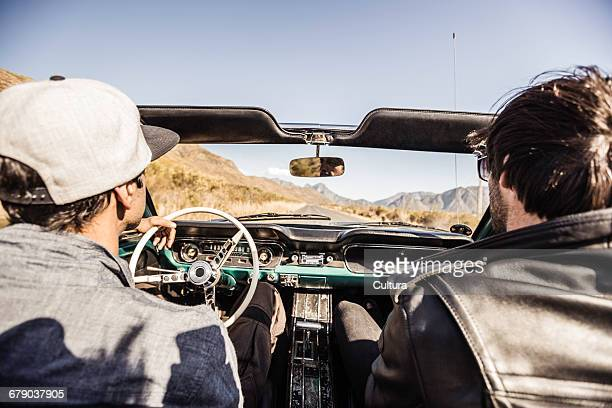 Over shoulder view of two men on the road driving convertible, Franschhoek, South Africa