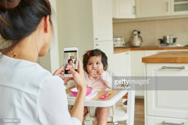 Over shoulder view of woman photographing baby daughter in high chair