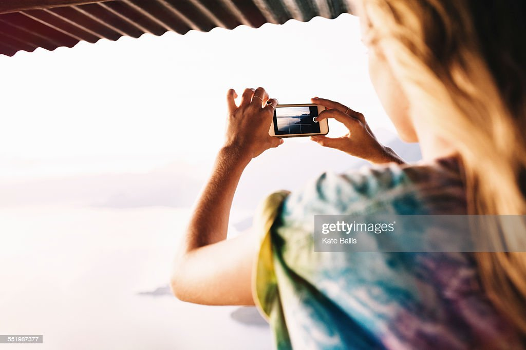 Over shoulder view of young woman photographing Lake Atitlan, Guatemala