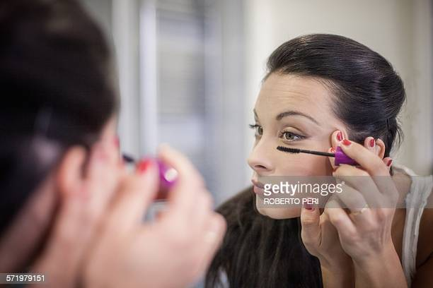Over the shoulder mirror image of young woman applying mascara