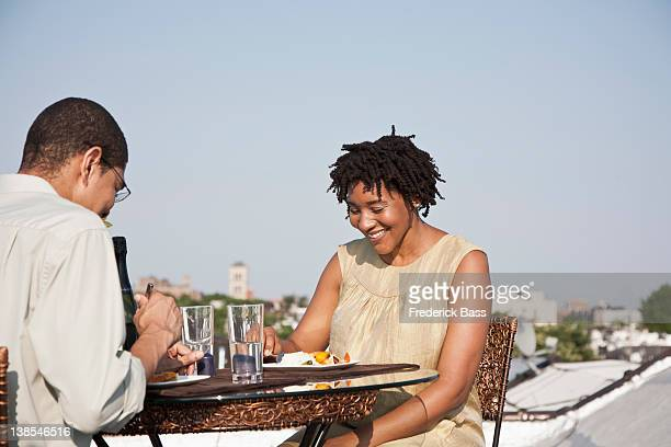 Over the shoulder view of a couple eating a meal on a rooftop terrace