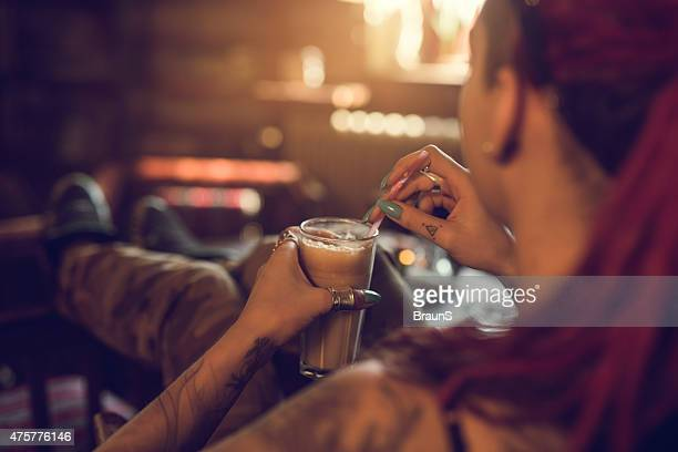 Over the shoulder view of a woman holding coffee.